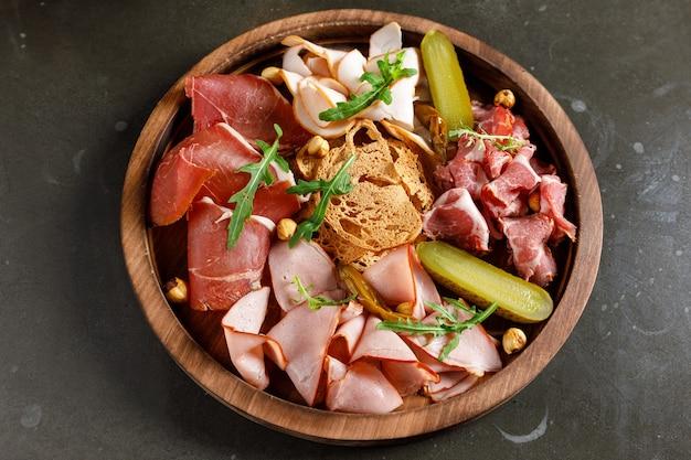 Разделочная доска с ветчиной, салями, сыром, хлебными палочками и оливками на темном каменном фоне. вид сверху