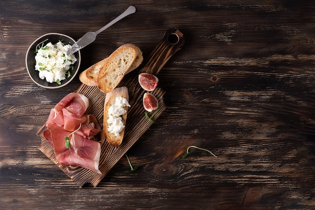 Cutting board with prosciutto, slices of bread and ricotta on a dark wooden background, italian ham with figs, copy space.