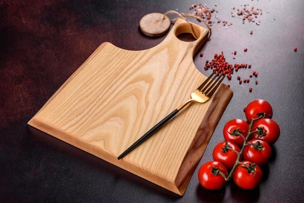 Разделочная доска с солью, специями и травами на темном фоне бетона. готовим здоровую пищу