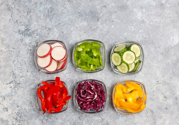 Cutting board with slices of colorful bell peppers on light surface. sliced sweet peppers in different colors, vegetable salad ingredient, cooking healthy food, top view
