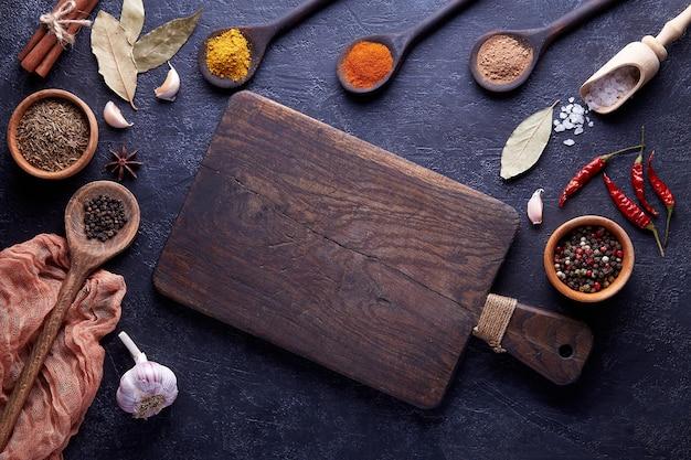 Разделочная доска со специями и зеленью для приготовления мяса на темном фоне