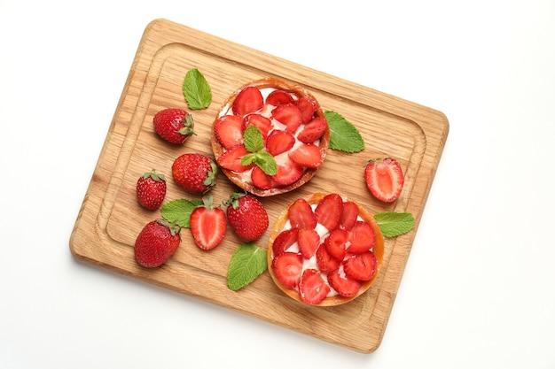 白い背景の上のイチゴのタルトとまな板。