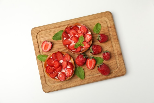 Cutting board with strawberry tarts on white background.