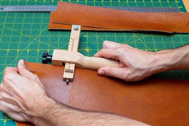 Раскрой коричневой кожаной полоски для ремня с помощью полосового резака. мастерская кожгалантереи.
