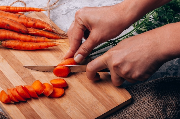 Cutting carrots in the kitchen closeup