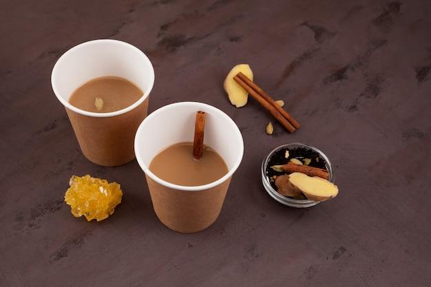 Нарезка чая или мумбаи нарезка чая - популярного индийского уличного чая. сваренное молоко и заварка с имбирем и специями. вкусный напиток из придорожного кафе в бумажных стаканчиках.