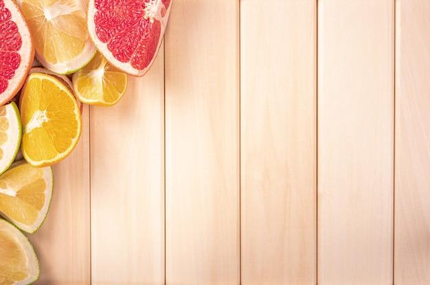 コピースペースで木製の背景に柑橘系の果物をカットします。木の板の柑橘系の果物のコーナー。