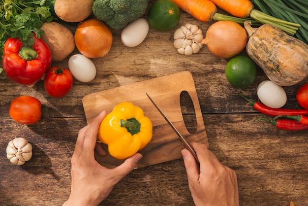キッチンで料理人の男性のナイフの準備新鮮な野菜のサラダを切る