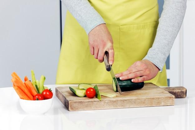 背景にきゅうりと野菜を切る