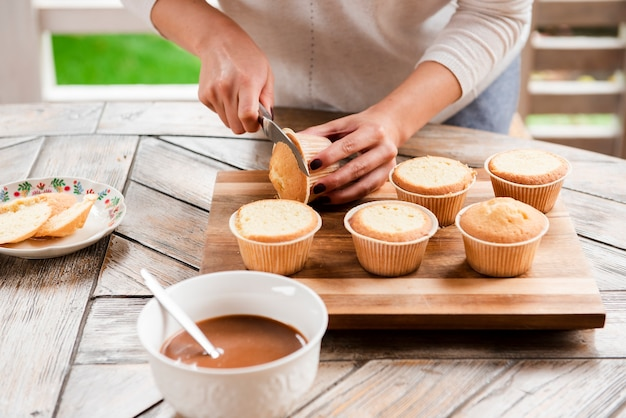 Cutting cupcake and bowl of filling