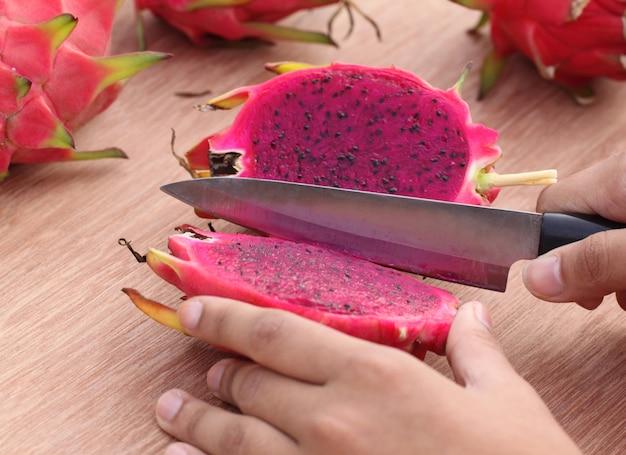 나무 표면에 칼로 용 과일 자르기