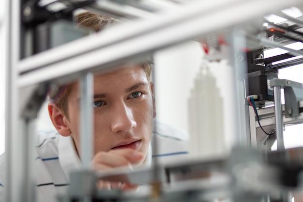 최첨단 혁신. 3d 프린터에 밀접하게 기대어 작은 마천루가 만들어지는 매력적인 젊은 남자