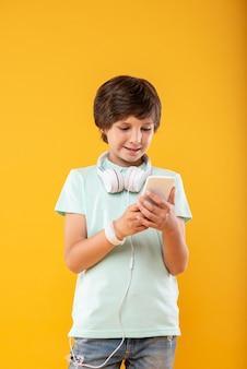 最先端の技術。彼の電話を使用し、彼のヘッドフォンを身に着けている陽気な黒髪の男子生徒