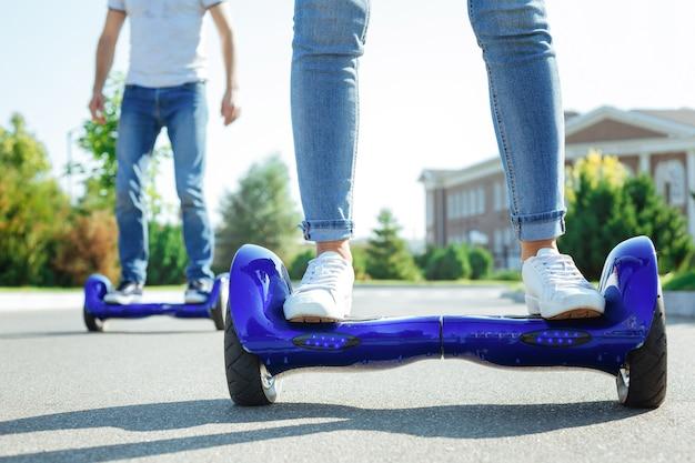 최첨단 기술. 남자가 백그라운드에서 다른 하나를 타고있는 동안 파란색 자체 균형 스쿠터에 서있는 여성 다리의 닫습니다
