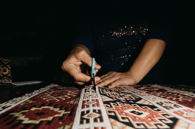 Cutting ethnic carpet with scissors