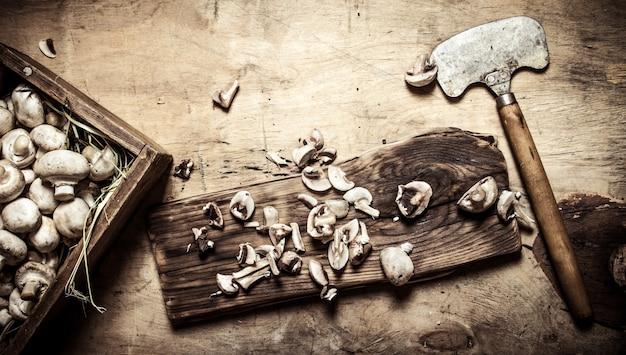 新鮮なキノコの古い手斧を切る
