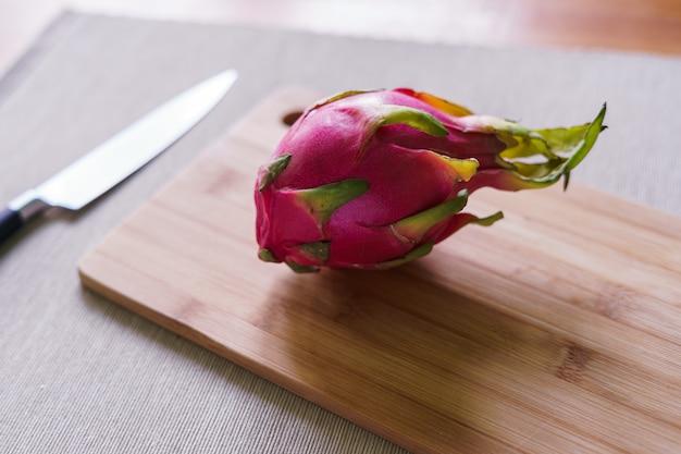 Cutting fresh pitaya or dragon fruit on wooden table