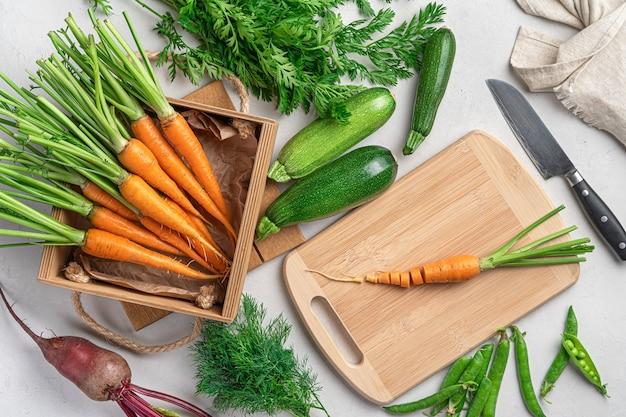 Нарезка свежих овощей на сером фоне. приготовление овощного блюда. вид сверху.