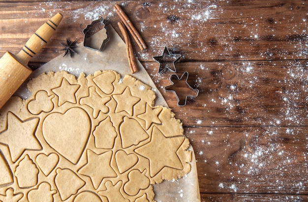 Cutting ginger biscuits in different shapes on a wooden background