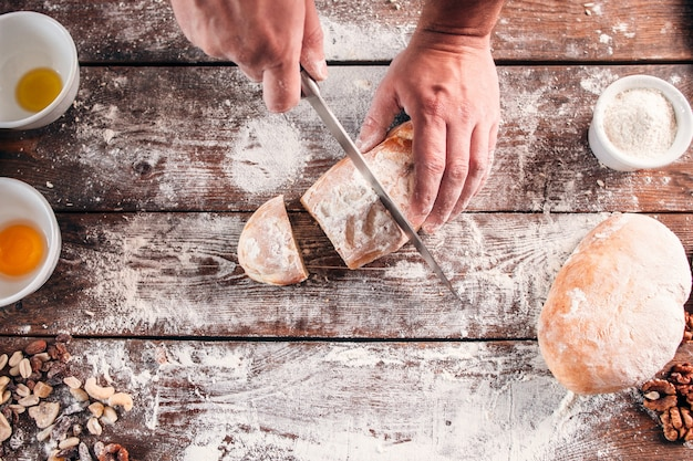 Cutting homemade bread on kitchen table