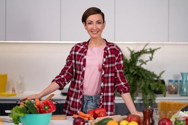 Резка ингредиентов на столе молодая женщина готовит обед, стоя на кухне. здоровая пища