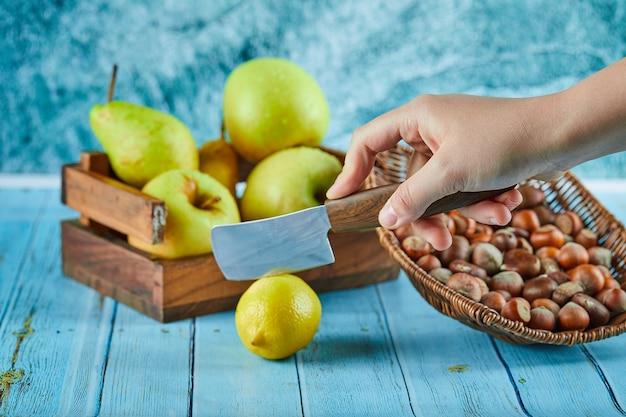 Разрезание лимона на синем столе с деревянной корзиной яблок и орехов.