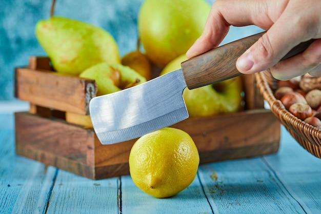 リンゴの木製バスケットで青いテーブルにレモンを切る。