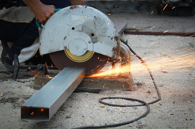 Cutting of a metal pipe with splashes of sparks.
