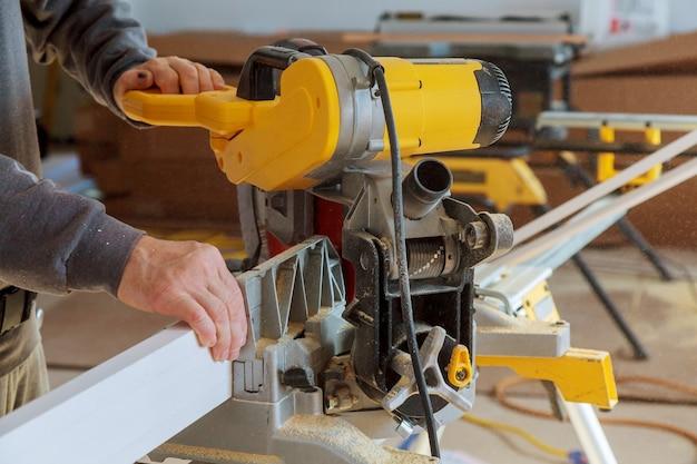 Резка молдинга для ремонта нового дома в стадии строительства отделочные работы в рабочем вырезает молдинг