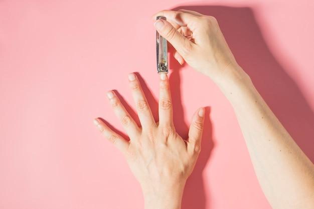 Обрезка ногтей сверху с розовой поверхностью