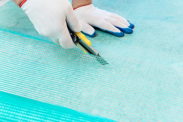 Cutting off a piece of fiberglass mesh with a knife