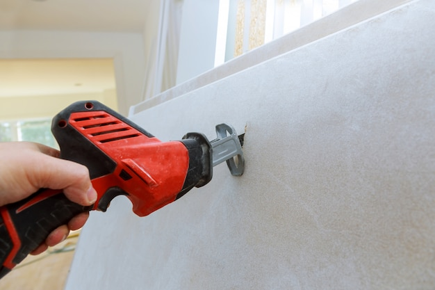 Cutting plasterboard of drywall hand with grunge dirty saw