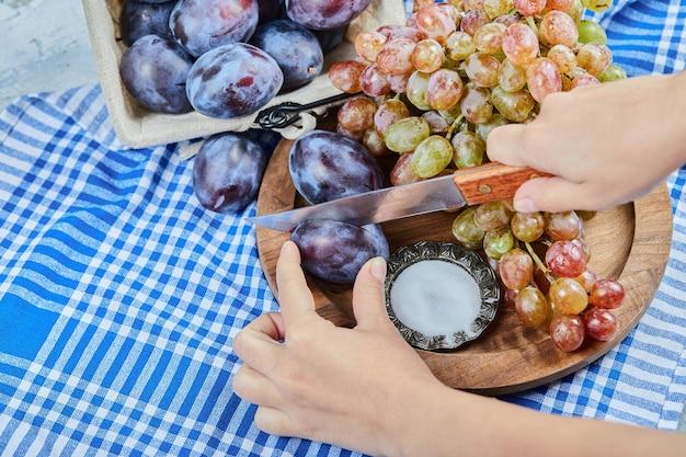 Нарезка сливы с гроздью винограда на деревянной тарелке. фото высокого качества