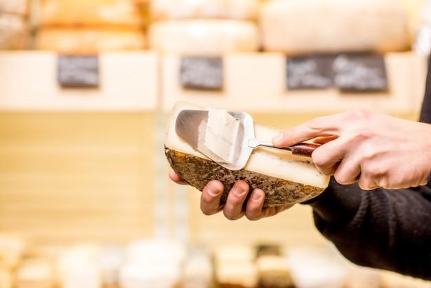 チーズショーケースの背景にスライサーで味付けしたチーズを切る