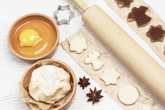 종이에 초콜릿을 뿌린 곰팡이로 모양의 쿠키를 자릅니다. 계란, 반죽, 계피 스틱 및 롤링 핀. 평면도.
