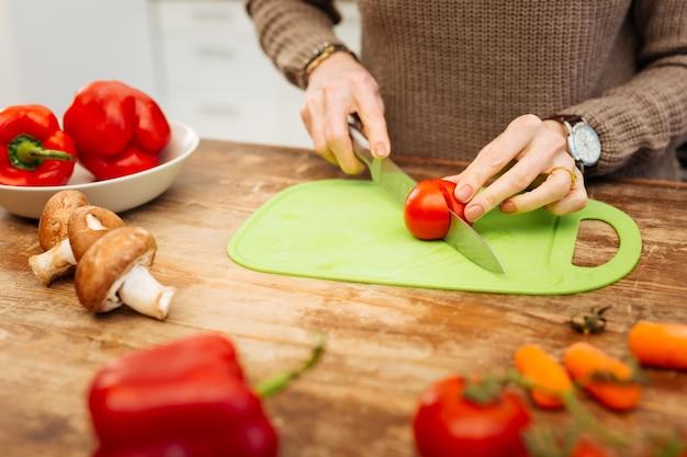 トマトを切る。小さな部分にトマトを刻みながら夕食の準備をしている暖かいセーターを着たきちんとした女性