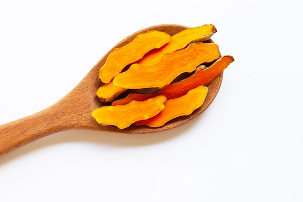 Cutting of turmeric roots on wooden spoon on white surface.