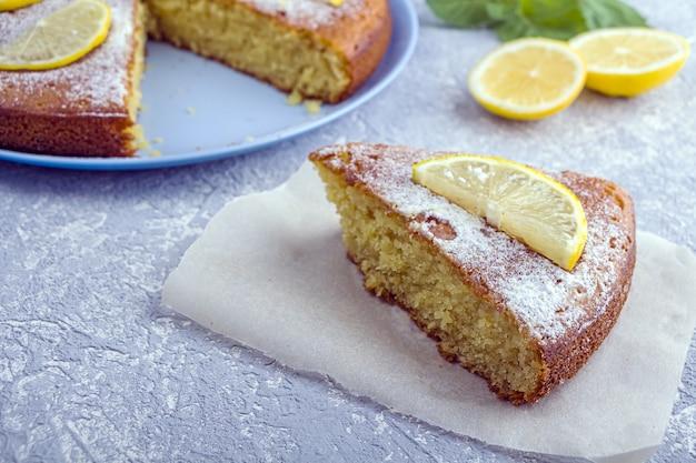 Нарезанный кусочек свежеиспеченного лимонного пирога, пирога или торта из манной крупы на тарелке, подаются дольками лимона и мятой