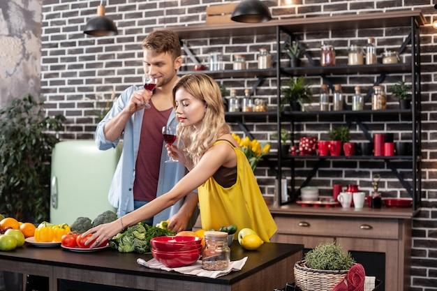 야채 절단. 샐러드 야채를 자르고 그녀의 잘 생긴 남자와 와인을 마시는 사랑하는 여자 친구를 돌보는