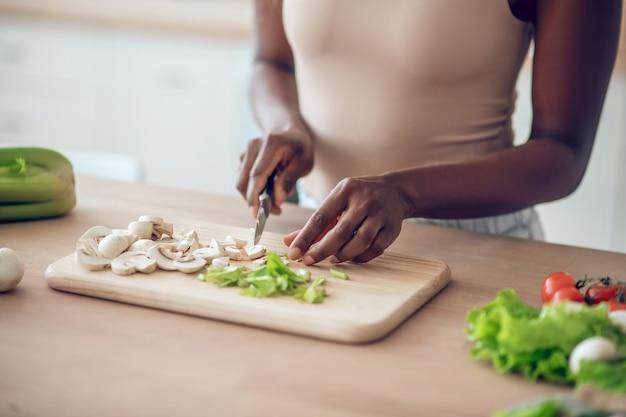 野菜を切る。ナイフで野菜を刻んで台所のテーブルの近くに立っているカジュアルな服を着たアメリカ人女性の手