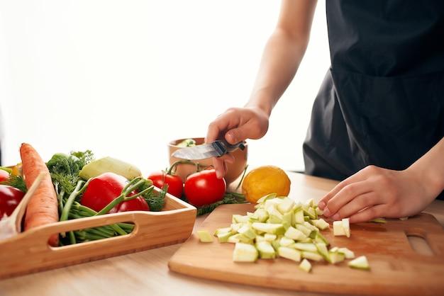 まな板のキッチンのクローズアップで野菜を切る新鮮な