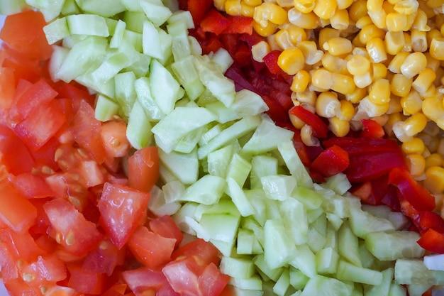 Нарезка овощей помидорами, огурцами и кукурузой.