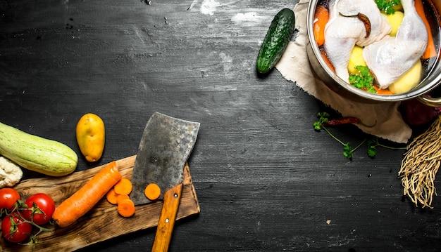 野菜を斧でチキンスープに切る。