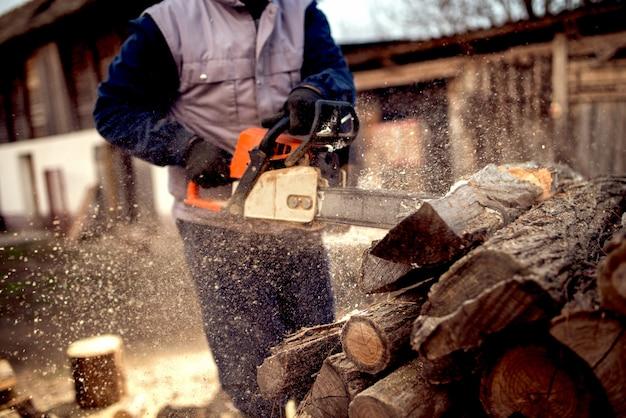 Cutting wood with chainsaw at backyard, lumberjack work professi