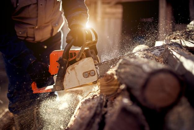 Cutting wood with chainsaw at backyard, lumberjack work profession.