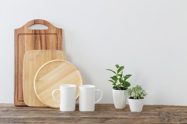 Резка деревянных досок, белых чашек и зеленых растений на деревянной полке