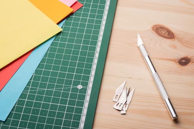 切断作業。アートワーク。カッティングマットの近くに刃のセットとアートワーク用の紙のセットがある新しい鋭いメス