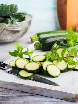 Cutting zucchini on wooden board