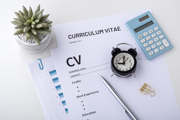 Cv with pen and clock on white desk