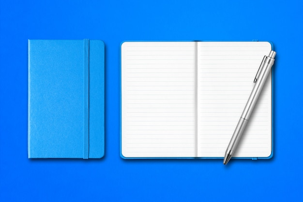 Cyan closed and open notebooks with a pen isolated on blue surface